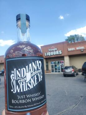 """A bottle of whiskey that's in front of a liquor shop named """"Triangle Liquors"""" beside a sign that reads, """"beer. wine.""""."""