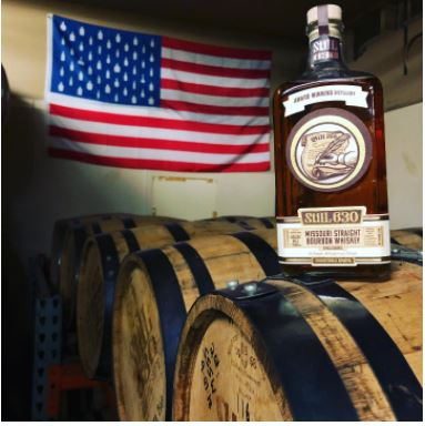 A bottle of  whiskey placed on top of whiskey barrels with the American flag hanging on the wall behind it.