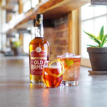 Old Hamer 100 Proof Single Barrel Straight Bourbon Whiskey on a table beside two glasses full of whiskeys on the right.