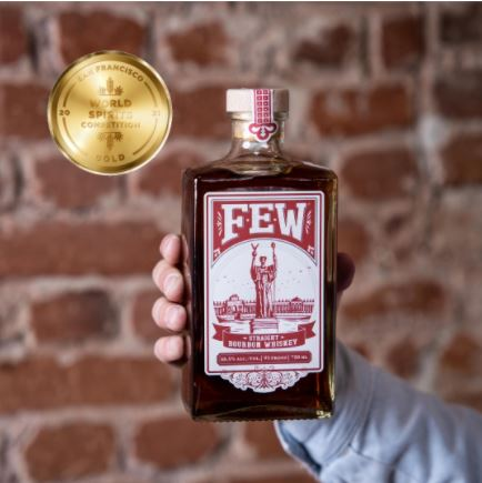 A bottle of FEW Spirit's American Straight Whiskey held by one hand in front of a brick wall background.