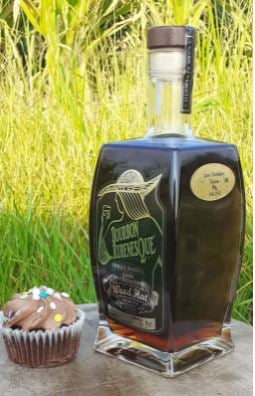 A bottle of Rubenesque on a stone tablet outdoors with a chocolate cupcake beside it.