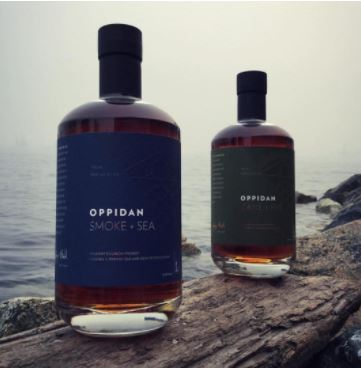 A shot of two bottles of Oppidan Smoke + Sea Bourbon on the shoreline.