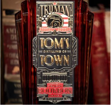A bottle of Truman's Special Reserve Bourbon in front of other spirits out of focus in the background