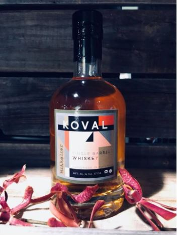 A bottle of KOVAL Mikkeller Single Barrel Whiskey on top of a wooden bench with flowers in the foreground.
