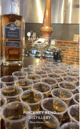 A bottle of Pinckney Bend Distillery's Rested American Whiskey behind a group of whiskey glasses on a table.