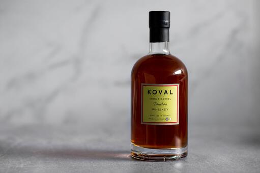 A bottle of KOVAL Bourbon Whiskey placed on a white marble floor with a blurred marble background.
