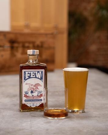 A bottle of FEW American Straight Whiskey beside an almost empty whiskey glass and a tall glass of beer.