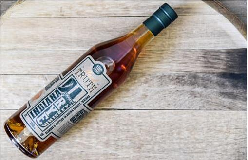 A Truth Hills Indiana Straight Rye Whiskey bottle is laid on a wooden table.