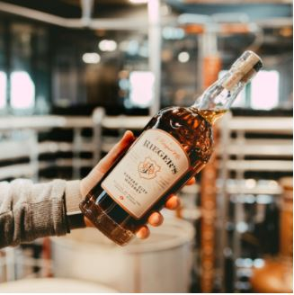 Someone standing out of frame holds a bottle of Rieger's Kansas City Whiskey inside a distillery.