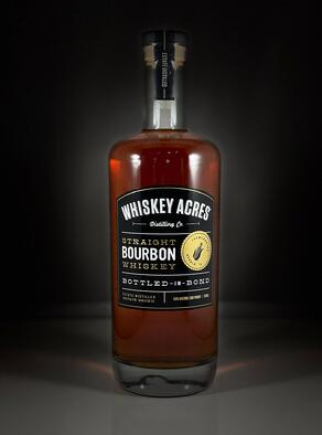 A bottle of Whiskey Acres' Bottled in Bond Bourbon on a black table with a black background.