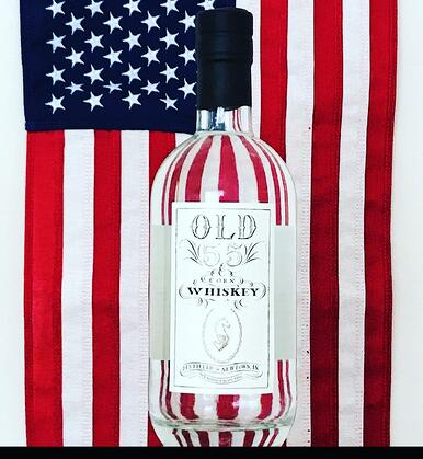 A bottle of Old 55 Corn Whiskey standing in front of an American flag backdrop.