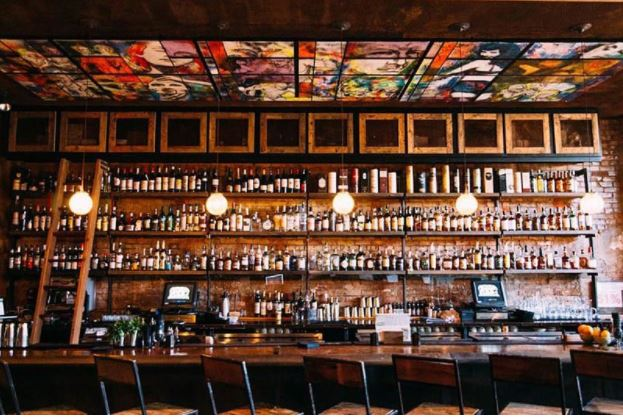 Well-lit bar, a line of chairs in front of the counter with wooden shelves behind the counter filled with spirits.