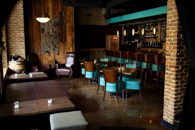 Well-lighted  bar and the wooden chairs are surrounded by brick walls and low lighting.