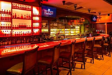 """Cocktail counter with empty chairs, full shelves, and two TVs mounted above the counter with the text """"blend"""" flashing"""