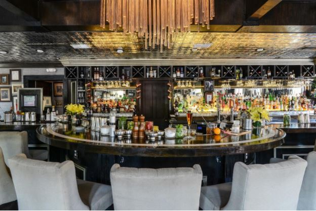 Brightly lit bar with white chairs, shelves are filled with spirits and brightly lit chandelier.