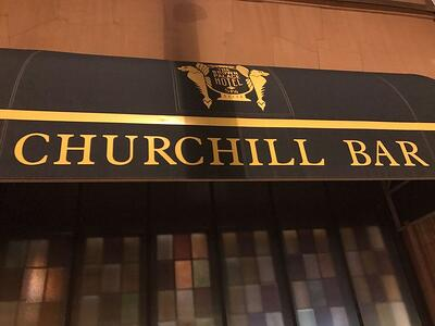 """Facade of the Churchill Bar with the signage above reads, """"The Brown Palace Hotel Spa and Churchill Bar"""
