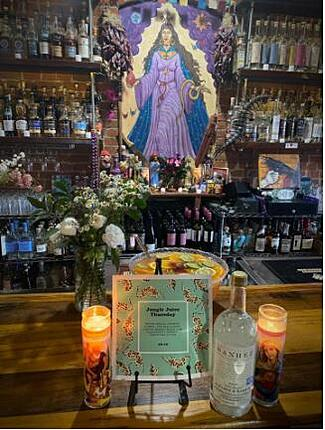 Tap list and punch on the counter, with Two lighted candles, a vase of white flowers & shelves with liquor bottles.