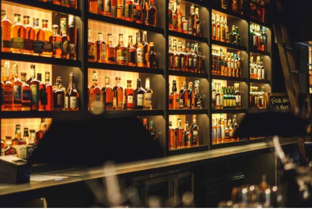 Seven Grand Denver's whiskey bar. The shelves are lit up and filled with liquor bottles behind the counter.