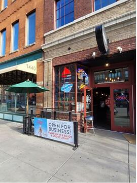 """Society Sports and Spirits' brick wall facade with signage """"Open for business! Come on in & enjoy a Coors light!"""""""