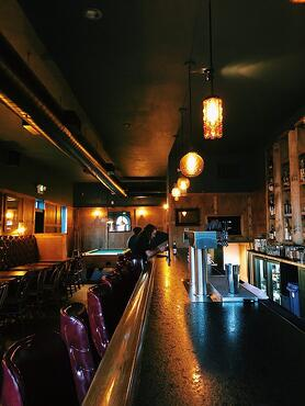 Sideways view of whiskey bar with lights turned on and hanging above the counter with maroon chairs in front.