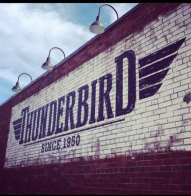 """facade with the text """"Thunderbird, since 1950"""" written on the brick red and white walls"""