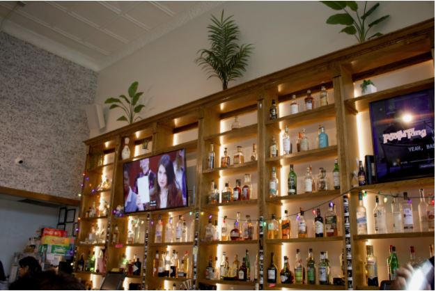 Two TV screens above the counter and the shelves behind are filled with spirits with plants above.