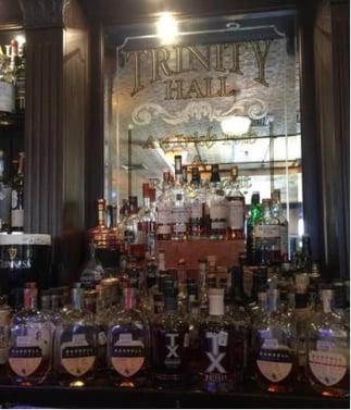 "Trinity Hall Irish Pub's spirits on display. Behind the bottles is signage that reads, ""Trinity Hall, An Irish Pub."