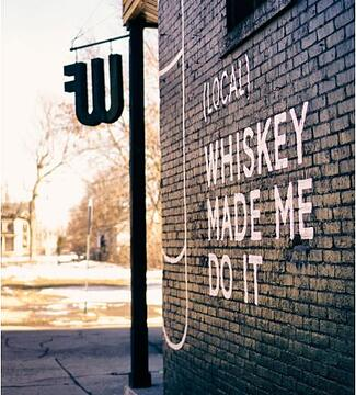 West Fork Whiskey's brick wall facade with the text (local) whiskey made me do it painted on it.