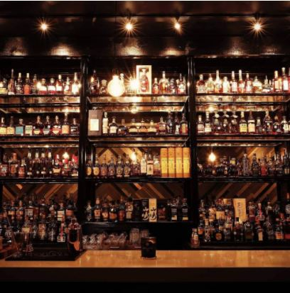 Whiskey bar at Whiskeys. It is dimly lit and shows the black shelves filled with spirits