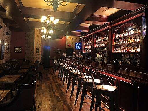 Wiseguy Lounge's bar with lights above empty chairs and shelves filled with bottled liquor behind the counter